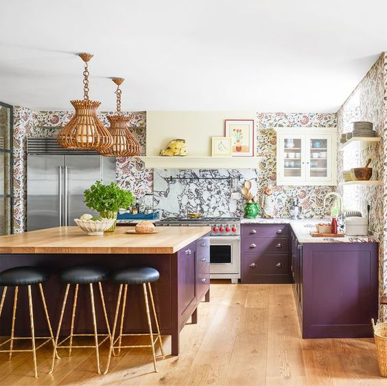 a whimsy kitchen with purple cabinets, a marble backsplash and floral print wallpaper plus rattan pendant lamps