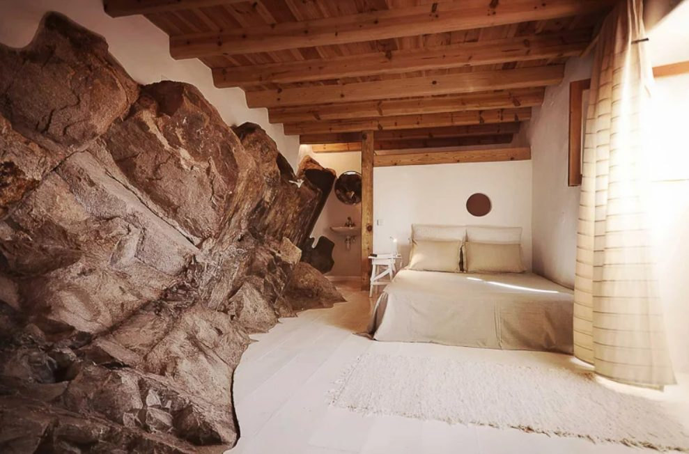 The bedroom features a fantastic rock formation and neutral decor and wood