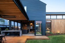 02 The house shows off a kitchen and dining space that can be opened to outdoors with sliding doors and an additional meal zone outdoors but under a roof