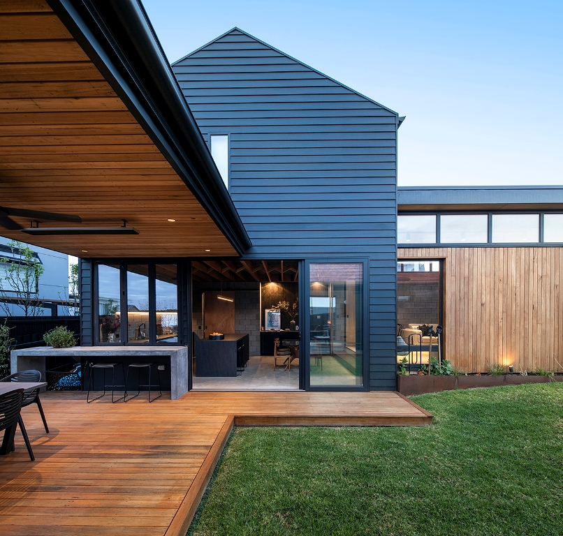 The house shows off a kitchen and dining space that can be opened to outdoors with sliding doors and an additional meal zone outdoors but under a roof