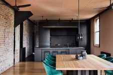 02 The kitchen and dining room are united, they feature exposed brick, blackened metal and stone and emerald velvet chairs soften the look