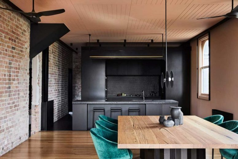 The kitchen and dining room are united, they feature exposed brick, blackened metal and stone and emerald velvet chairs soften the look
