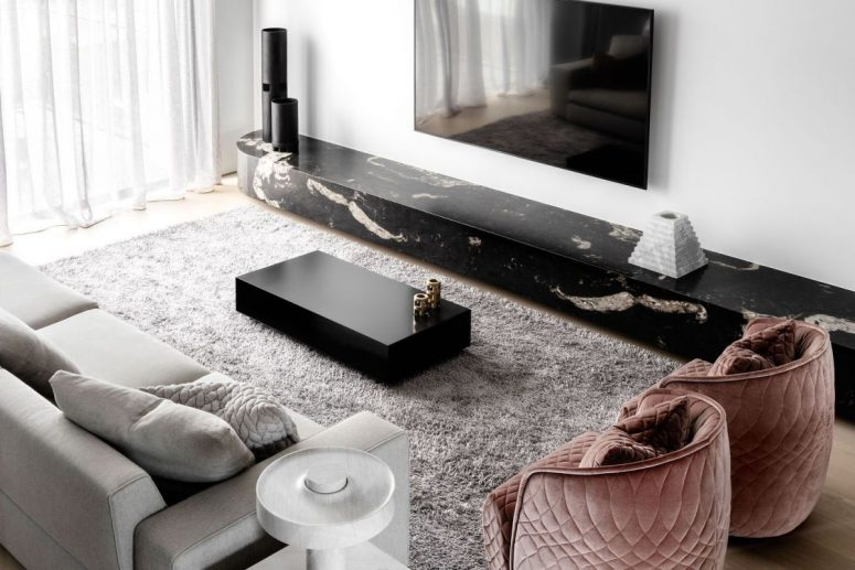 The living room is done with grey furniture, a black marble slba, pink velvet chairs and a fluffy rug and looks exquisite