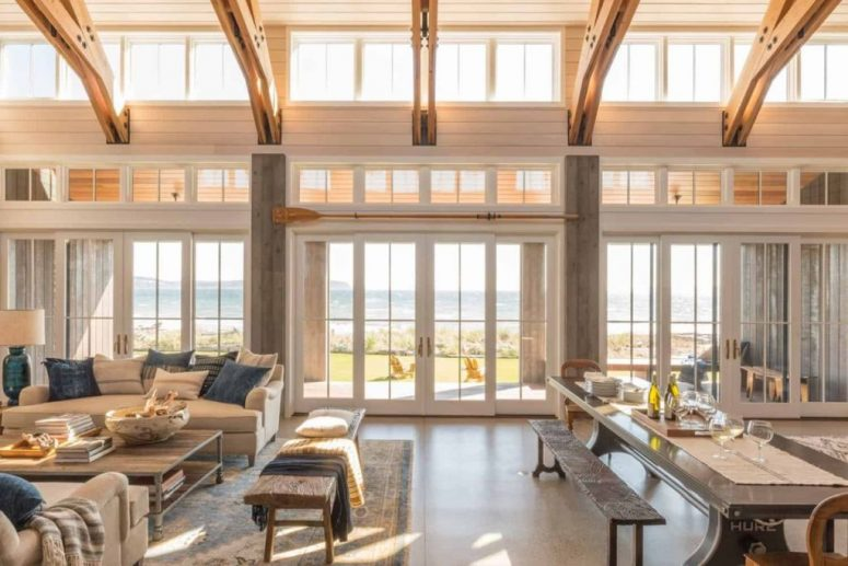 The main space is a large open layout with a living, dining room and a kitchen and lots of windows that flood it with light