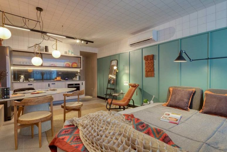The whole apartment is an open layout with a kitchen, a dining-working space and a sleeping zone