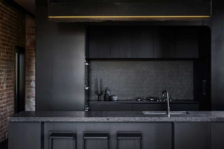 Black fixtures and a penny tile backsplash continue the moody color scheme