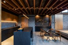03 The kitchen is done with concrete, light stained and matte black furniture, a black kitchen island and the dining space features a beautiful glass table
