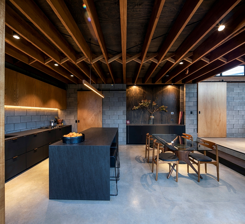 The kitchen is done with concrete, light stained and matte black furniture, a black kitchen island and the dining space features a beautiful glass table