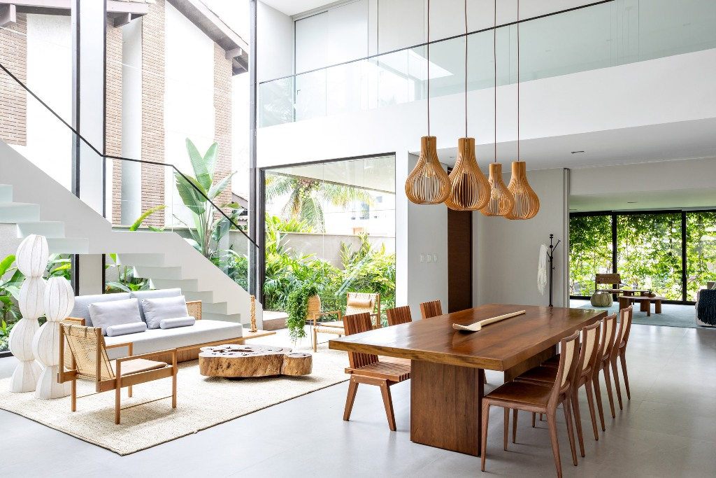 The living and dining spaces are united into one layout, with chic furniture and extensive glazing to bring as much light inside as possible