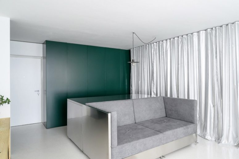 The sofa is also done with stainless steel, and the storage unit is sleek, in hunter green