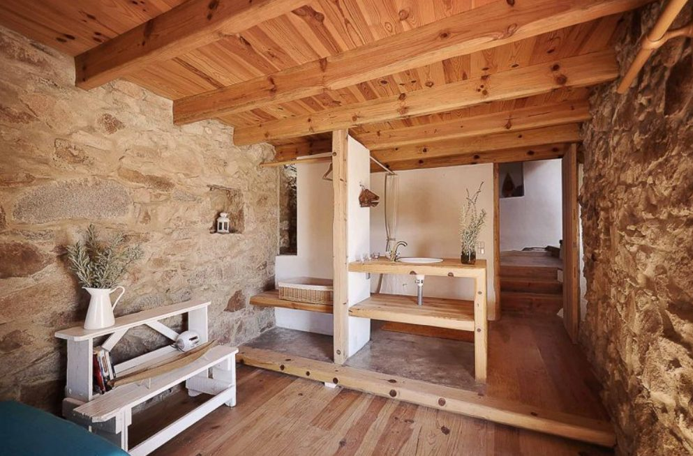 The bathroom is done with wood and stone, there's a vanity with a sink, a basket and a tub