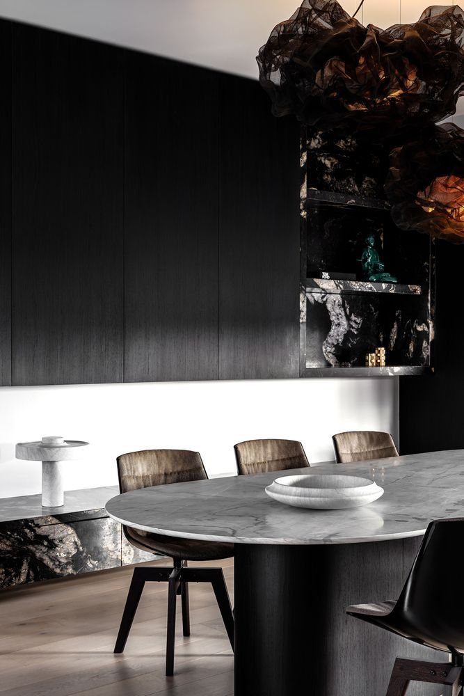 The dining room features black sleek cabinets, a marble top table, leather chairs and a black marble slab