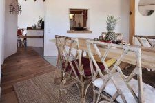 05 The dining space is done with a wooden table and rattan and twine chairs, there's a window to this space