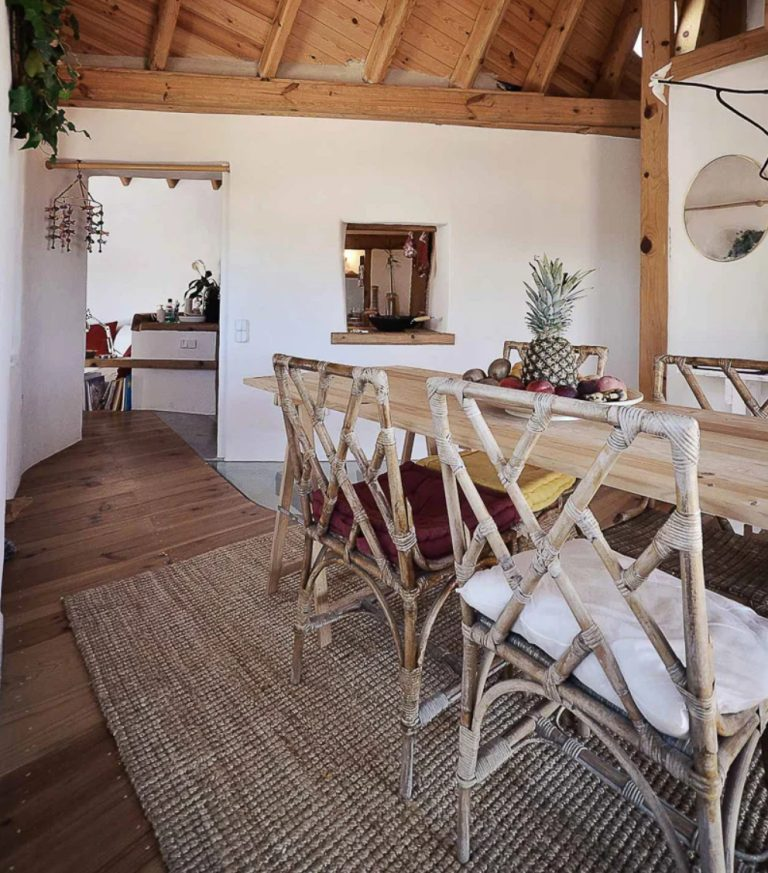 The dining space is done with a wooden table and rattan and twine chairs, there's a window to this space