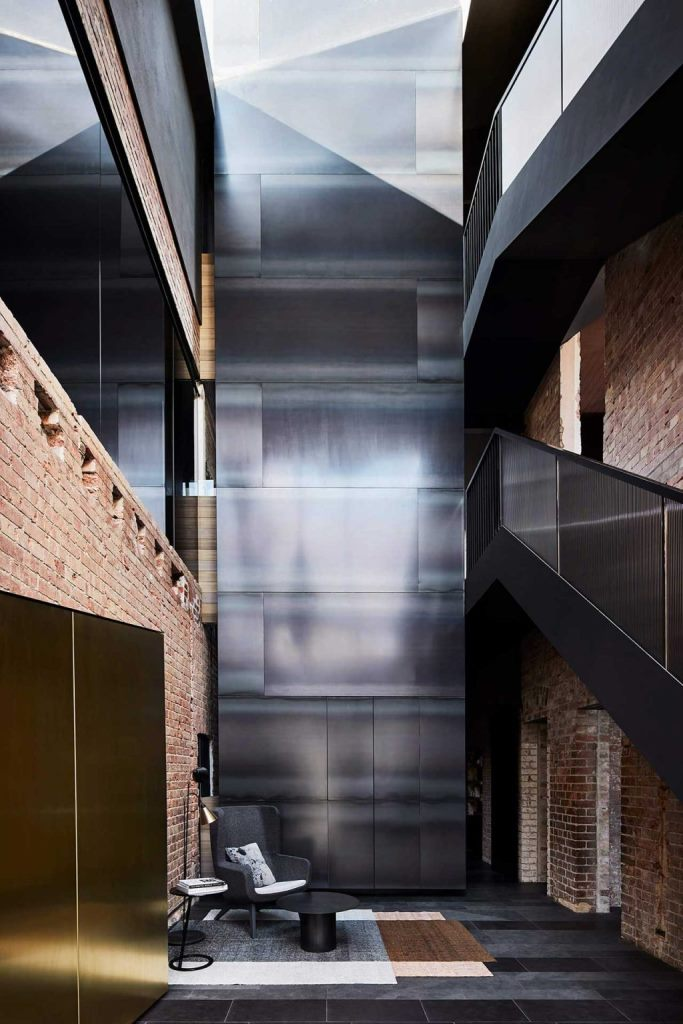 The entryway excites and astonishes with a polished metal wall, chic black furniture and brick walls