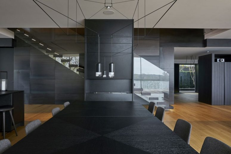The kitchen and dining space are done in black, with contemporary lamps and bold design