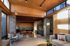 05 The kitchen opens up to a living room, with neutral comfy furniture and a concrete floor plus glazed walls