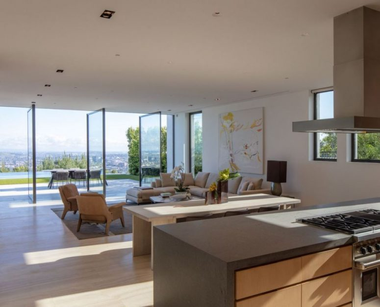 The living room is done with pivot glass doors that help the space to merge with outdoors