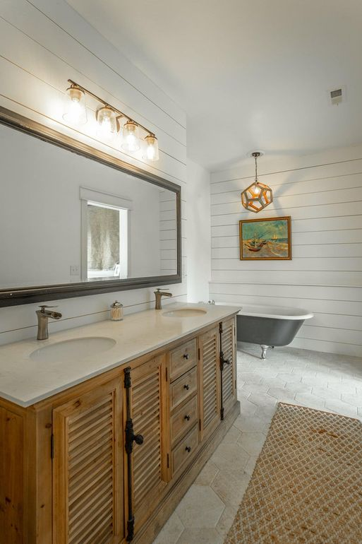 The master bathroom shows off hex tiles on the floor a wooden vanity, a rug and a black clawfoot tub