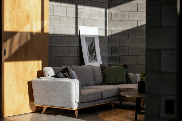 A jute rug, concrete walls, a metal table make the space catchier with textures and more welcoming