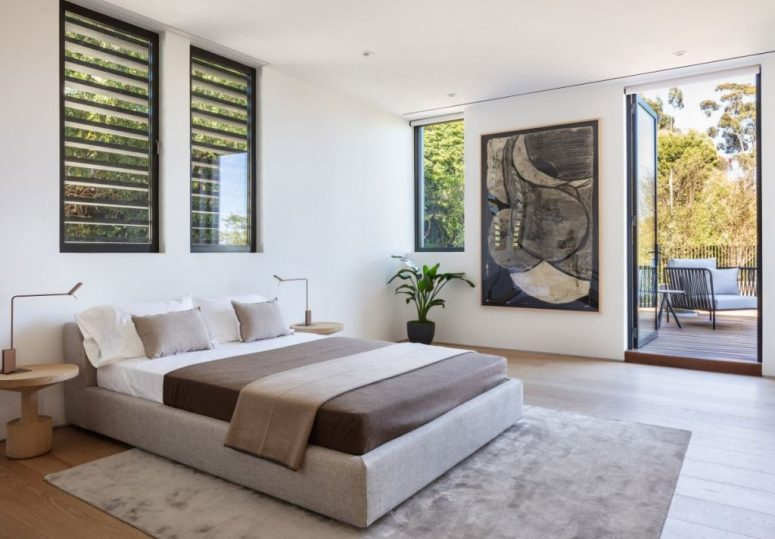 The bedroom is done in a neutral color scheme, with a statement artwork and there's an access to outdoors