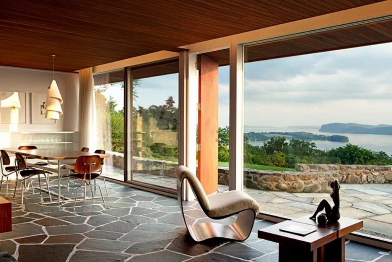 The dining and living room are united into one space with cool furniture, a rock floor and gorgeous river views