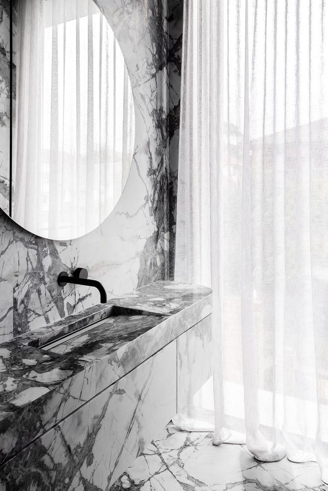 The powder room continues the idea with white marble all over and elegant minimalist decor