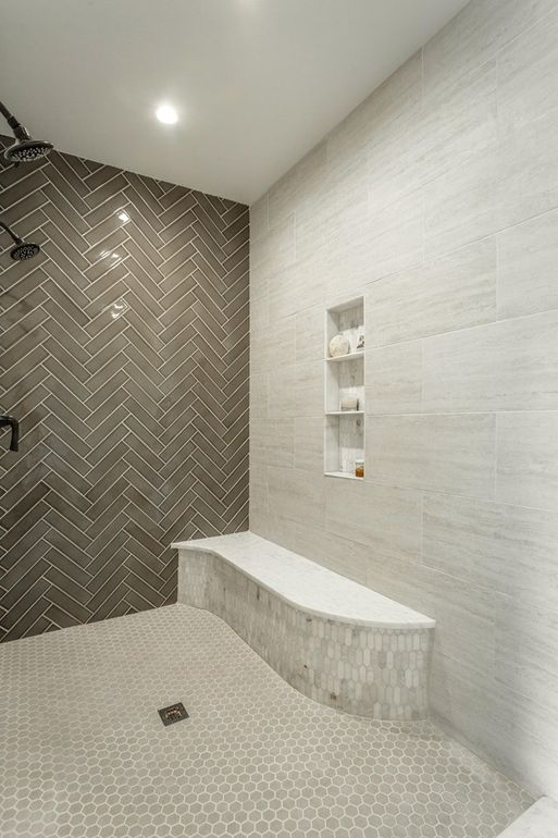 There's a large walk-in shower done with three different types of tiles