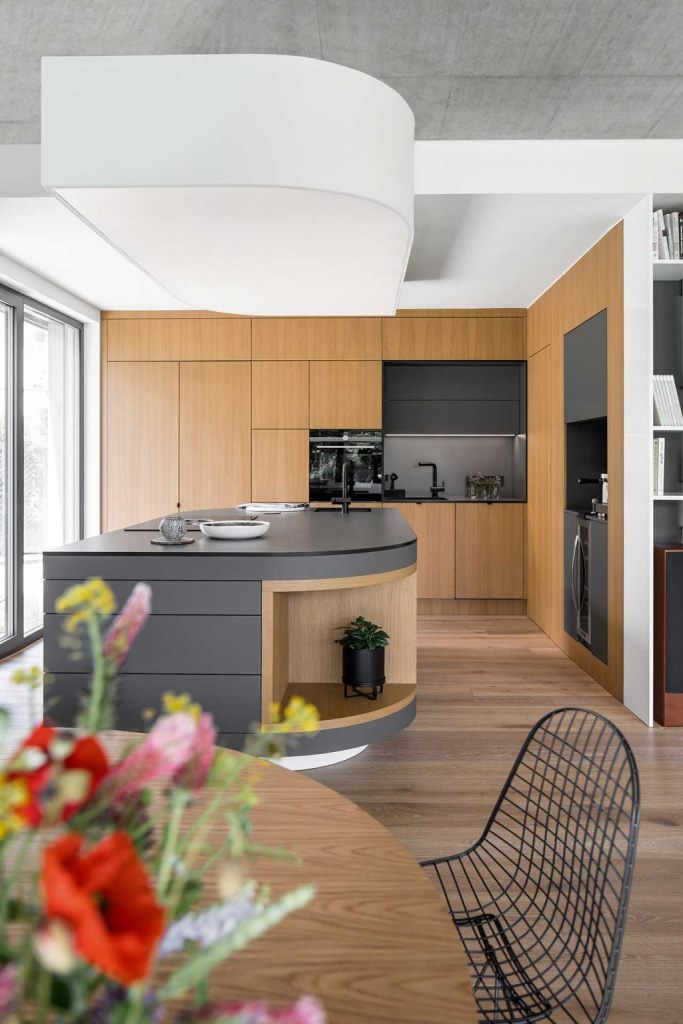 The kitchen is done with sleek cabinets and surfaces, with a concrete tabletop and a backsplash