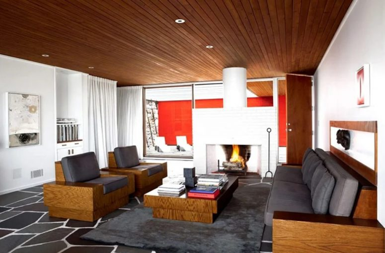 The living room shows off a large white hearth, grey furniture with stained wood parts