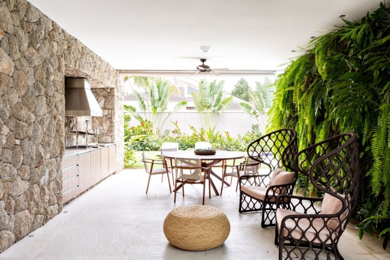 The outdoor dining zone is surrounded with a living wall and a stone wall