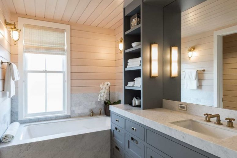 There's a large grey vanity and a bathtub clad with white marble