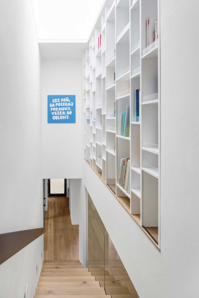 A giant bookshelf is placed over the stairs to use this awkward space, too