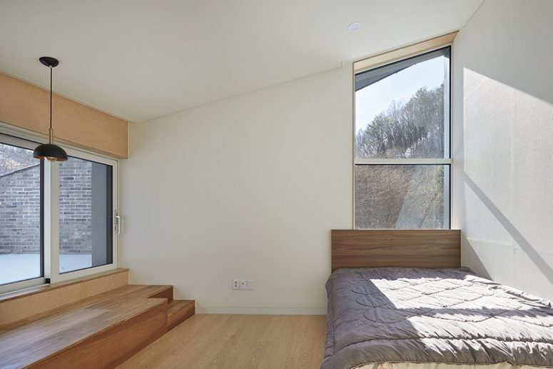 The bedroom is minimal, with a bed and some storage units and light plus lots of windows for the views