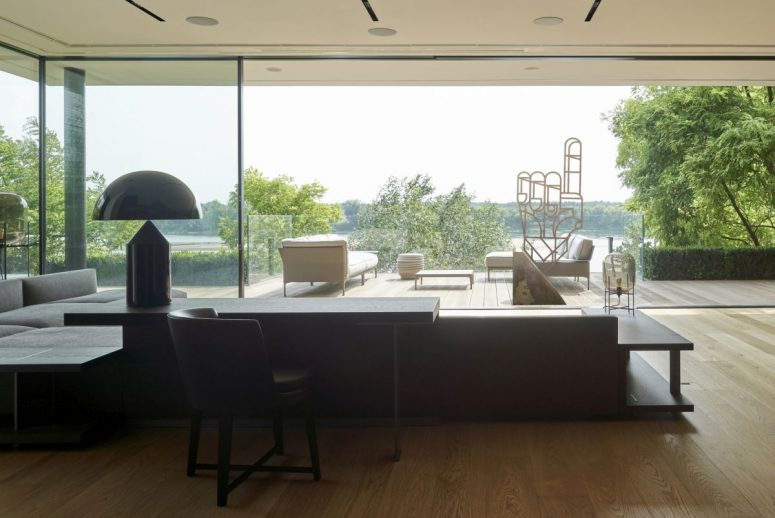 The living room is done with comfy grey and black furniture and can be opened to an outdoor terrace