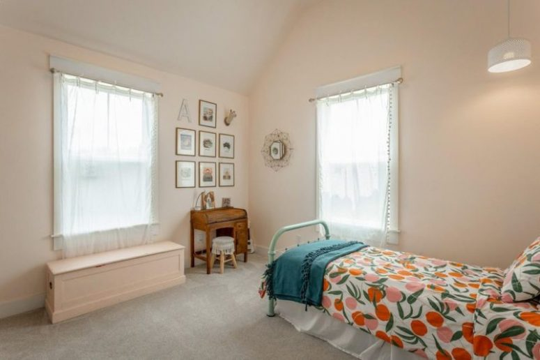 This bedroom done in blush shows off vintage furniture, a gallery wall and bright bedding