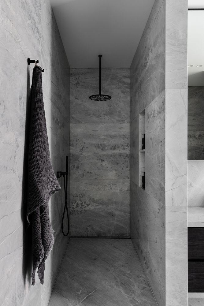 Soft grays create a calming and relaxing ambiance in this open walk-in shower