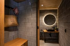 09 The bathroom continues the decor theme with concrete walls and floors, a lit up mirror and neutral stained wood