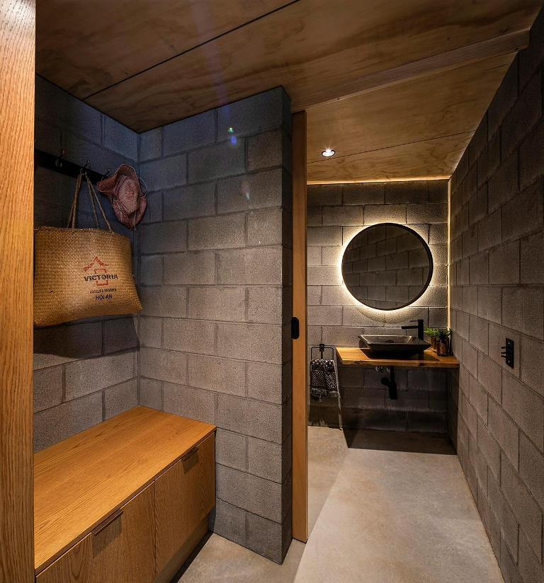 The bathroom continues the decor theme with concrete walls and floors, a lit up mirror and neutral stained wood