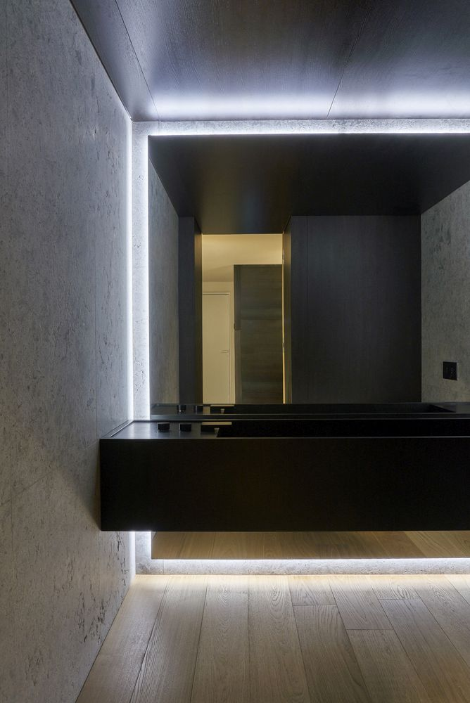 The bathroom is minimalist, with a black floating vanity, a mirror wall and built-in lights