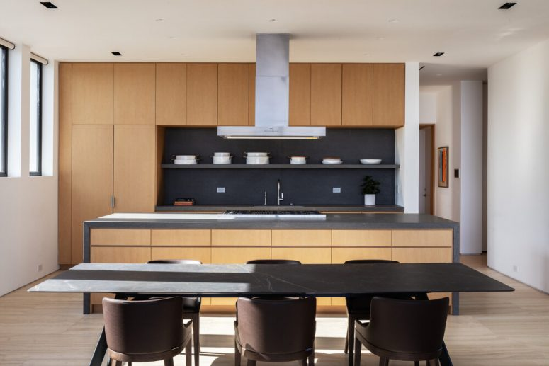 The kitchen is minimalist, with sleek neutral cabinets, a dark backsplash and there's a laconic dining space with a marble table
