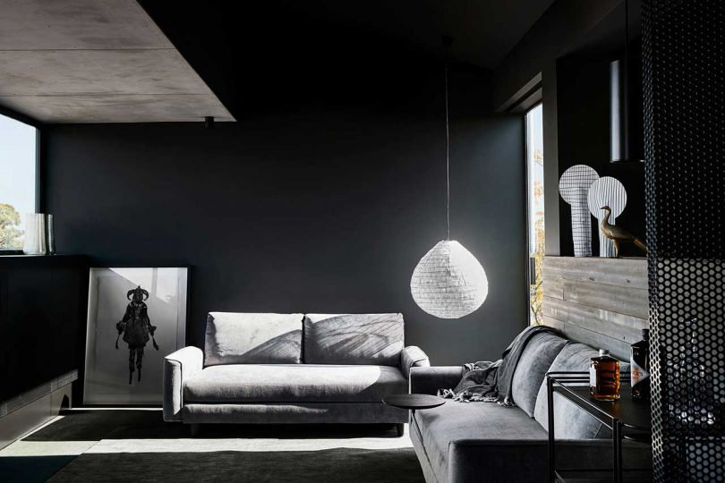 The living room is moody, yet gets enough natural light, comfy furniture is centered around the views