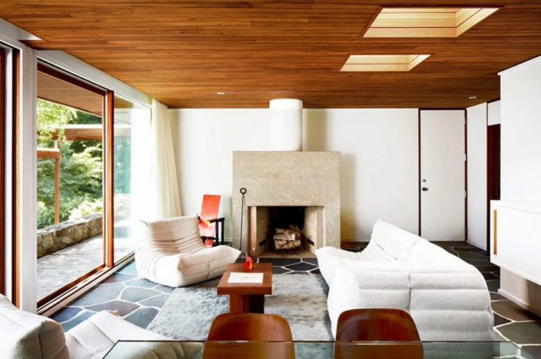 The sitting room is done in neutrals, with a stone hearth, white and neutral furniture and stained chairs