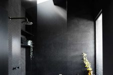 10 The black bathroom combines black penny and subway tiles and features windows