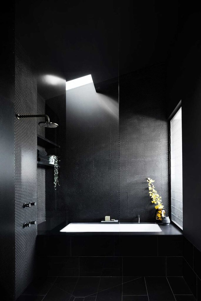 The black bathroom combines black penny and subway tiles and features windows