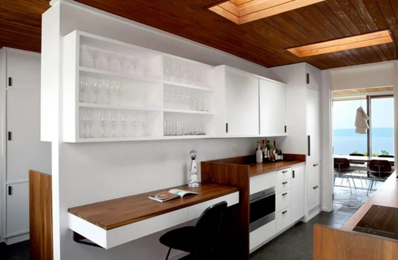 The kitchen shows off stained and white wooden cabinetry, a small working space with a floating desk