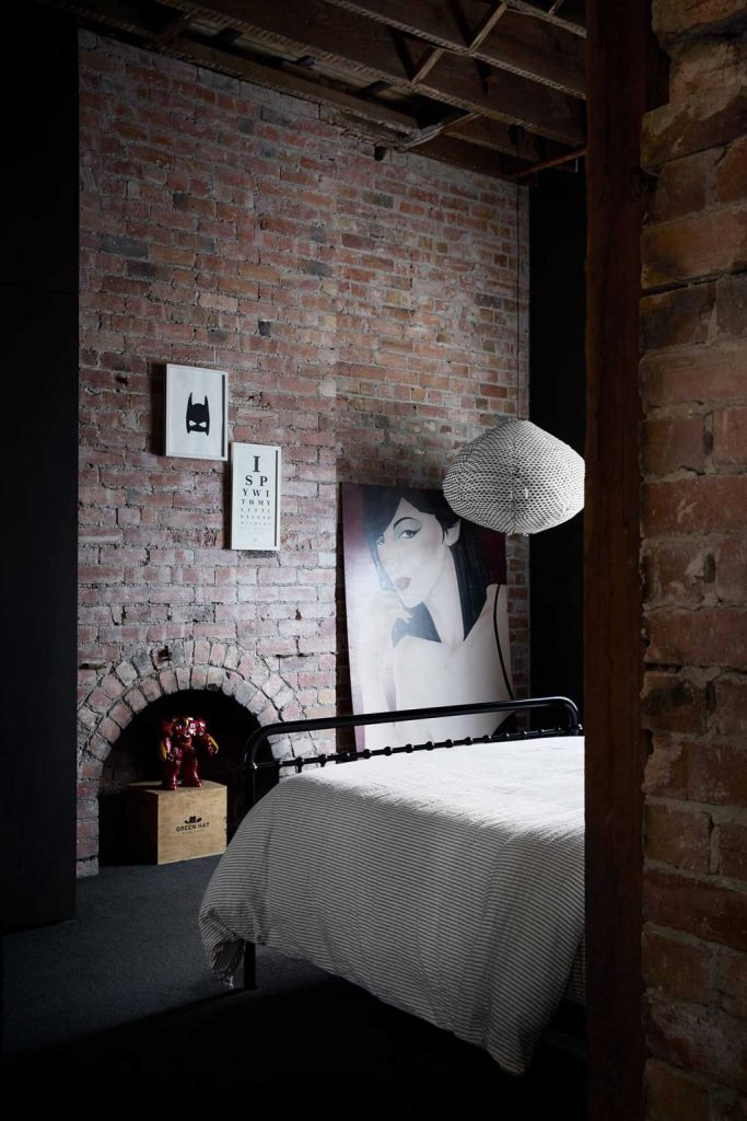 A guest bedroom shows off red brick, quirky artworks and a comfy metal bed