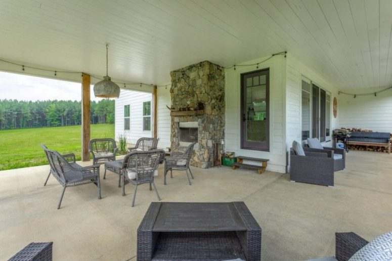 A large covered patio features a stone fire[;ace and woven furniture