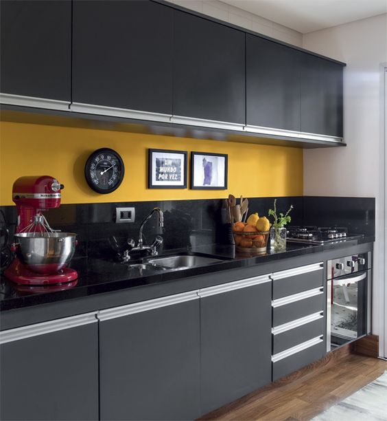 a bold graphite grey kitchen with a black and yellow backsplash and black stone countertops
