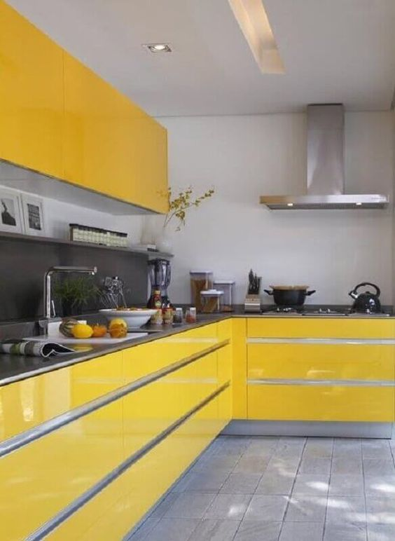 a bold minimalist kitchen with sleek yellow cabinets, a grey matte backsplash and countertops and stainless steel appliances